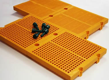 Two pieces of orange modular polyurethane screen meshes with six black bolts on them.