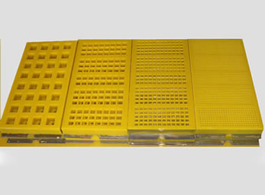 Four types of yellow modular polyurethane screen meshes with different opening sizes and hooks.