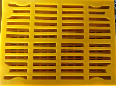 A piece of yellow modular polyurethane screen mesh with rectangular holes.