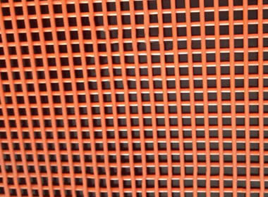 A piece of orange steel core polyurethane screen on the black background.