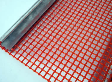 A piece of red steel core urethane screen with metal hook