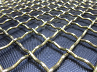 A piece of intermediate woven vibrating screen mesh on the blue background.