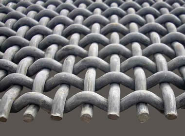 A piece of pre-crimped woven vibrating screen mesh on the gray background.